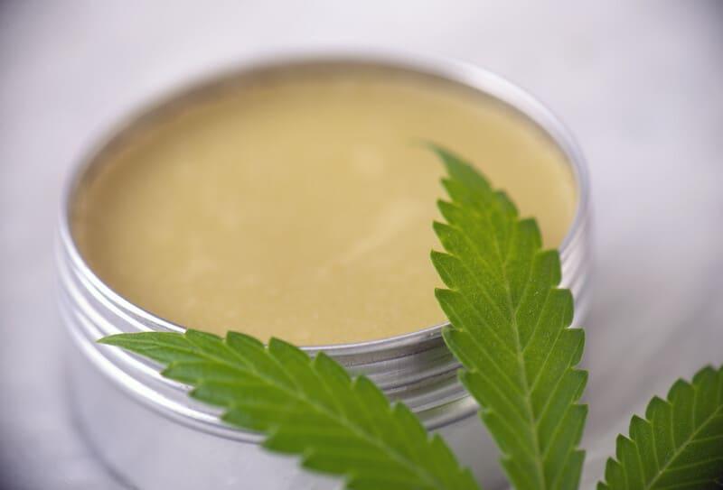 salve next to cannabis leaf, topical cannabis