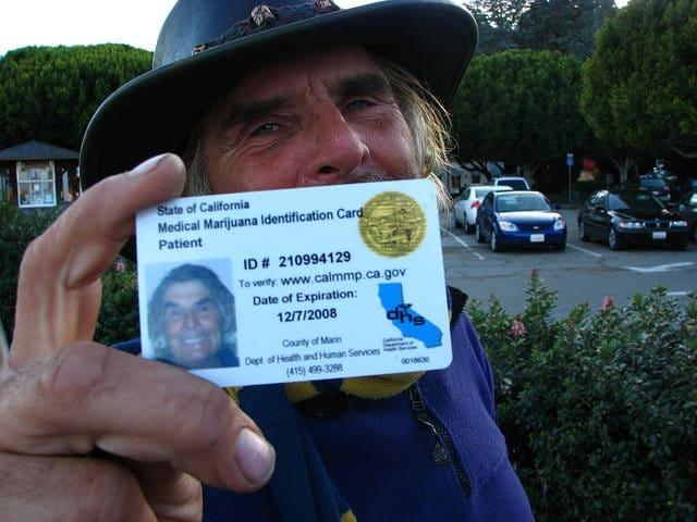 Getting a Medical Cannabis Card in Canada. Man holding his mmj card.