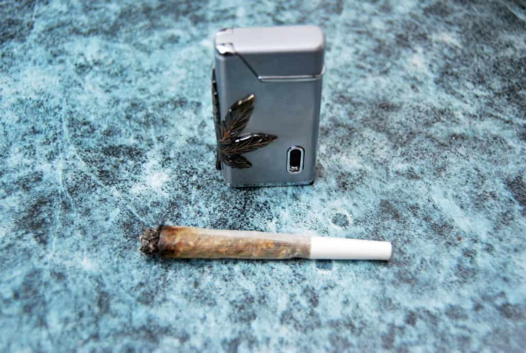 Ioint of marijuana, lighter with symbol of the drug