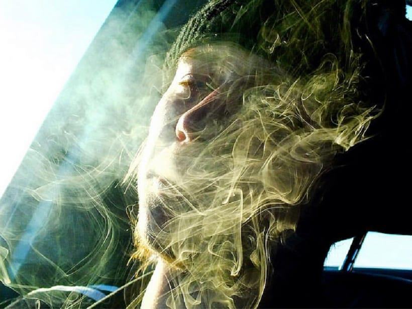 Guiding First Time Cannabis Smoker. Man with smoke in face.