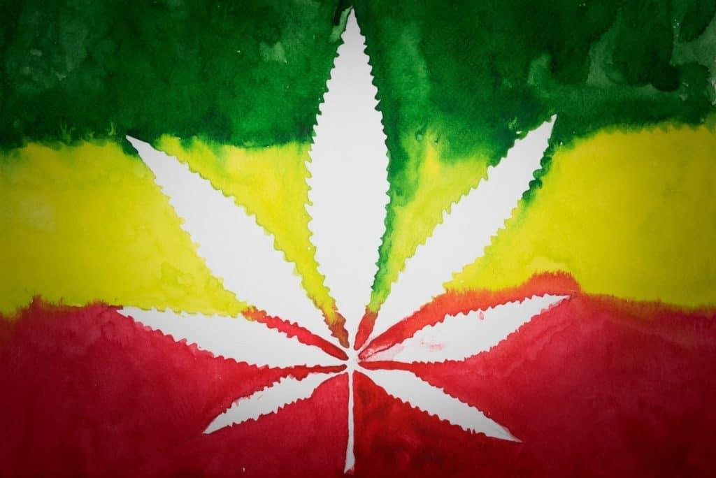 The Correlation Between Reggae and Marijuana Culture. Jamaican flag with a white marijuana leaf.