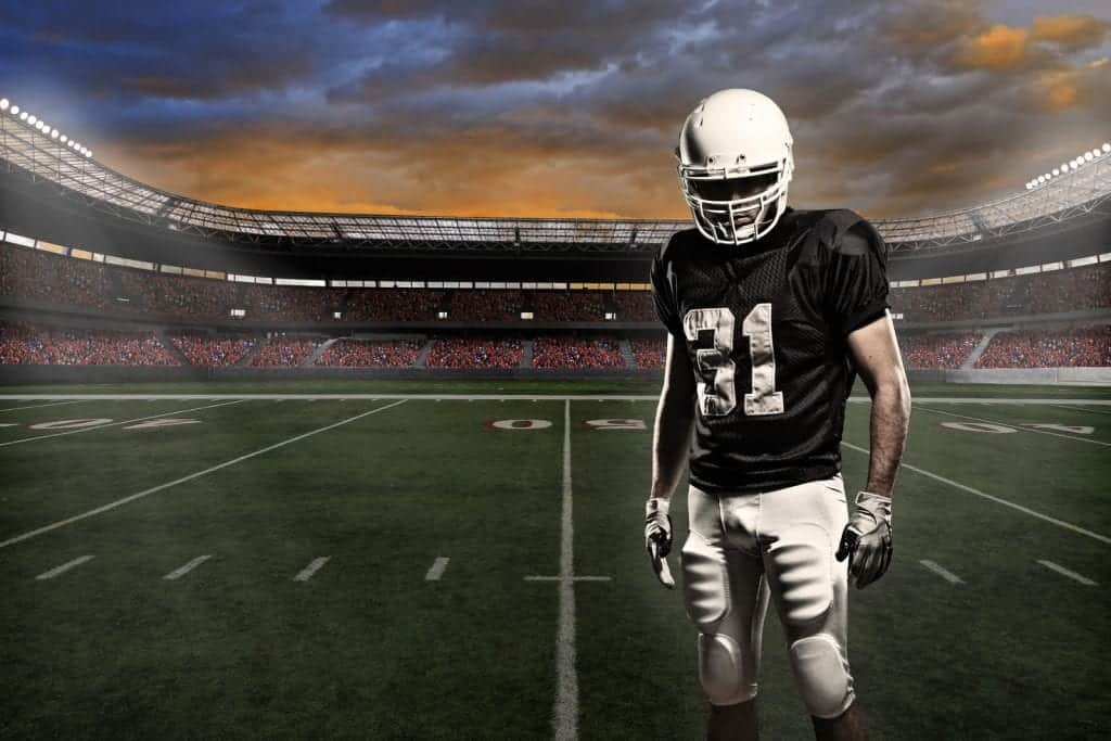 Learn Why Athletes Use Marijuana to Get Off Painkillers. Football player standing in stadium