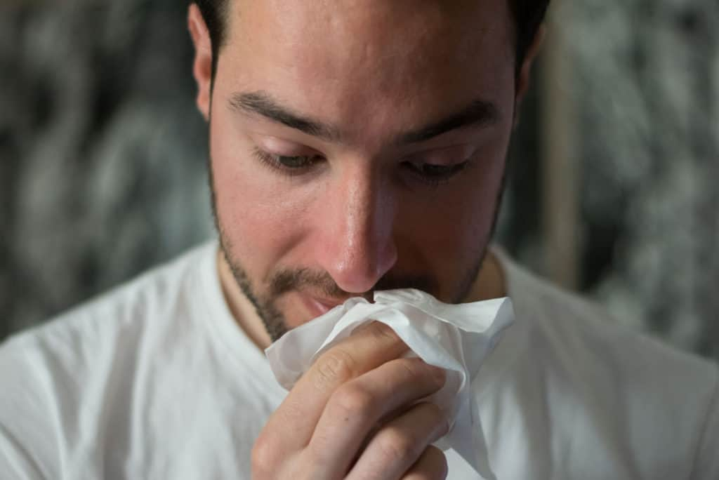 man blowing nose with tissue. Cannabis allergies? Allergic to weed?