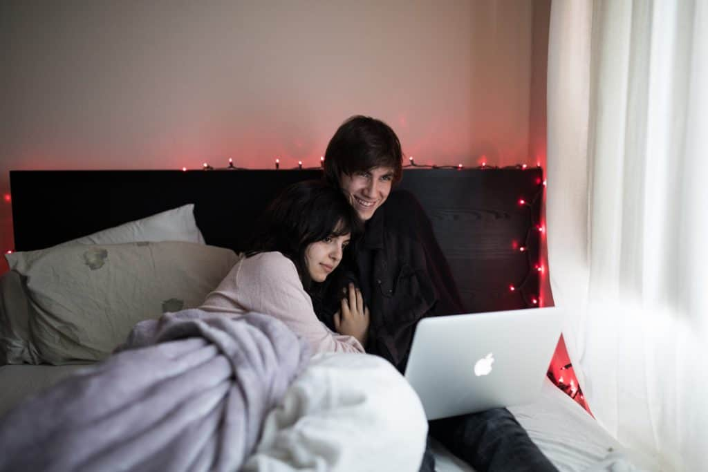 Couple watching Pot documentaries on Netflix in bed on an Apple laptop