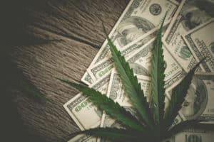 Coronavirus Federal Stimulus Bills: FAQ For Marijuana Businesses. $100 bills and marijuana leaves on wood surface.