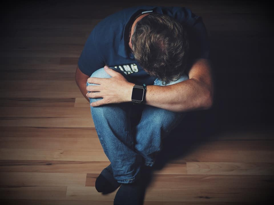 CBD for Fibromyalgia: Is it safe and successful? Man bent over on wood floor.