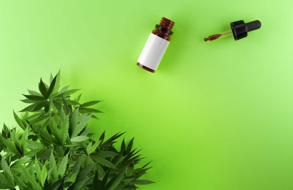 Is marijuana legal in Utah? Green background with marijuana leaf and tincture.