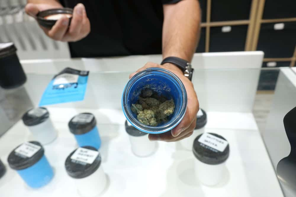 Pennsylvania Weed Jobs and Cannabis Careers. Man showing bud in a container.