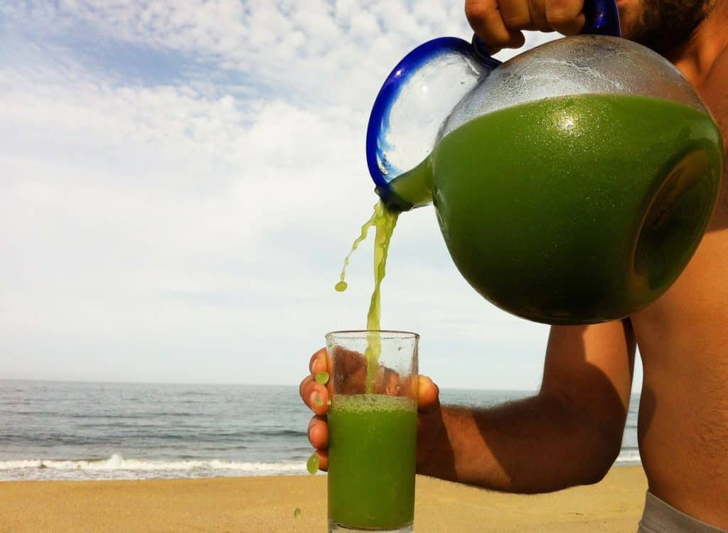 Does Juicing Raw Marijuana Help with Lupus? Green juice being poured into a glass.