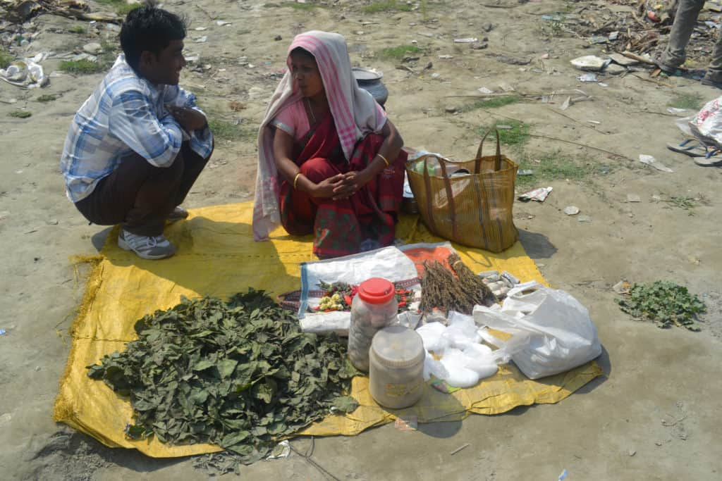 What exactly is bhang? Two people on a blanket with leaves.