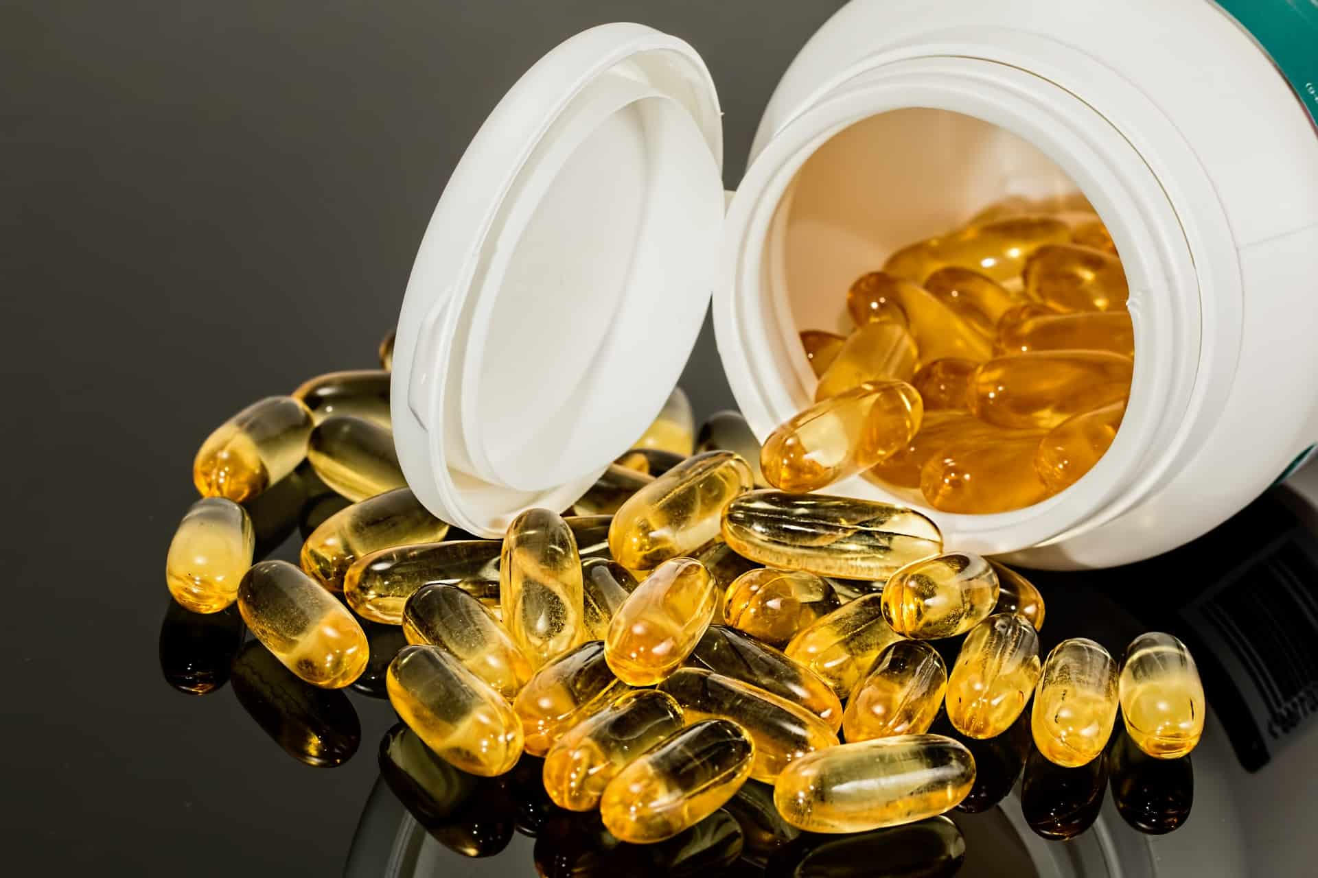 Is CBD a Medical Drug or a Dietary Supplement? Pills flowing out of bottle.