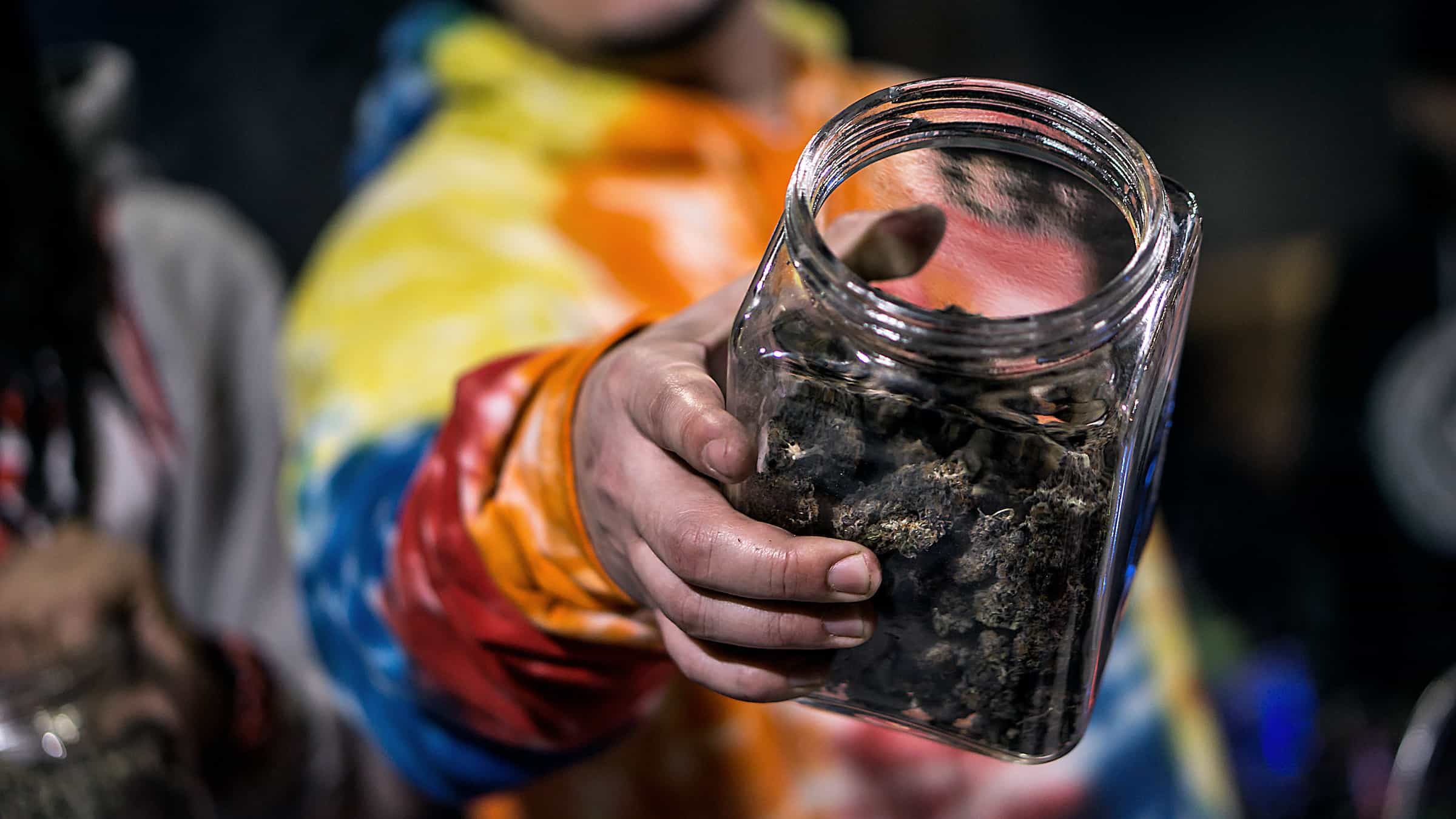 Budtender holding a glass jar of cannabis buds.