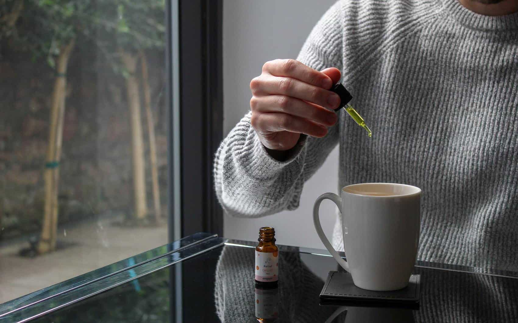 CBD for nerve pain being put in coffee cup.