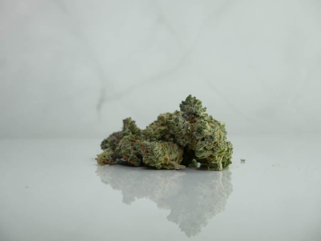 Best indica strain for sleep on white surface with a marble background.