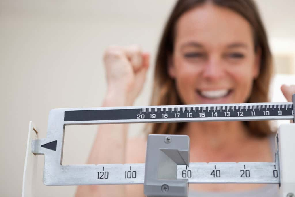 Girl on scale happy about her marijuana and weight loss results