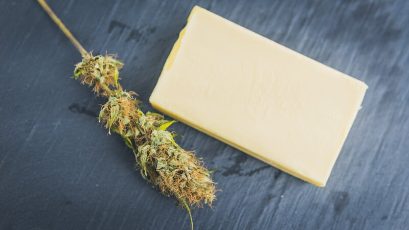 What is Budder with cannabis on grey table.