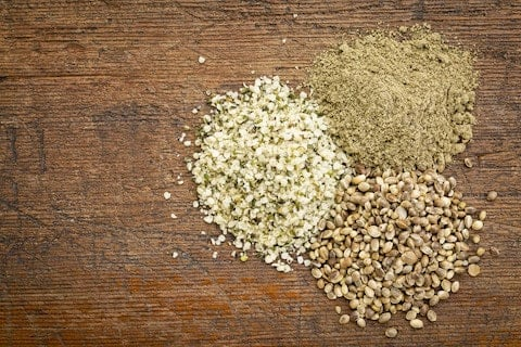 ananda hemp seeds, hearts and powder on wood table