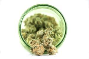 marijuana bud in glass jar on white surface, dream n sour strain