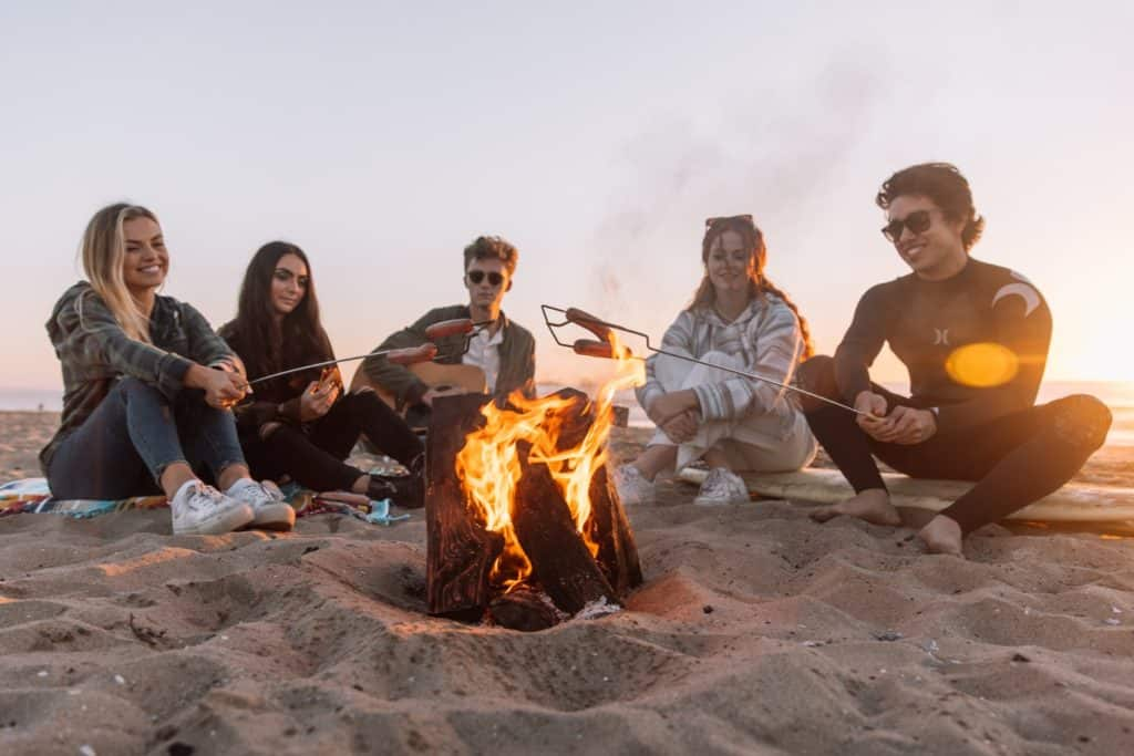 people sitting around a bonfire on the beach, new cannabis strains for summer