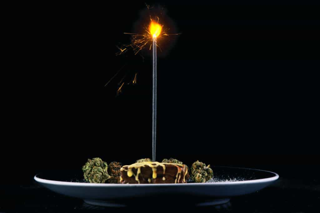 pot brownie plate with different marijuana buds and birthday candle, birthday cake