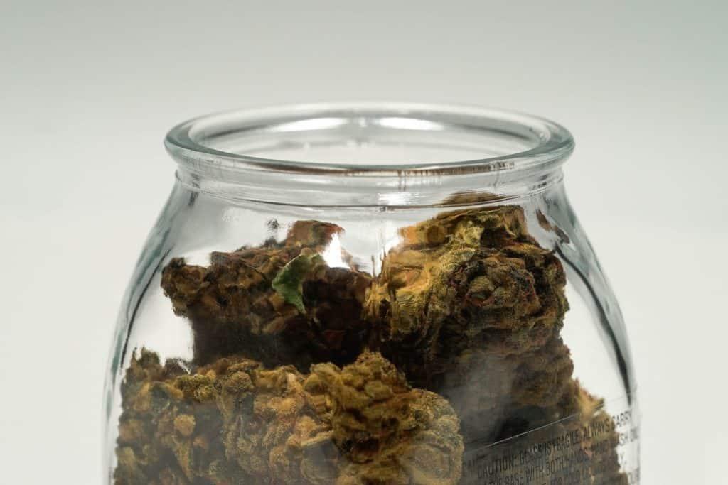 brown cannabis buds in glass jar, marijuana legalization