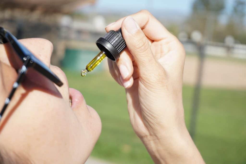 women taking a drop of cbd oil, liquid gold cbd