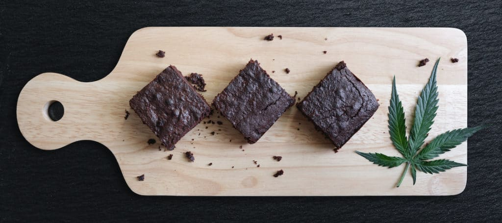 Dark Chocolate Homemade Brownies Infused with Medical Cannabis, with Marijuana leaf on wooden tray, weed recipes