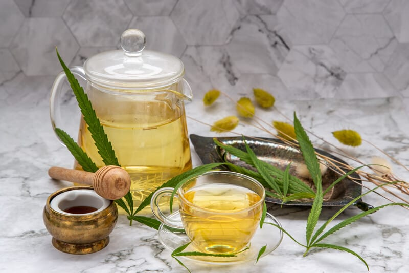 marijuana leaves surrounded by cbd tea