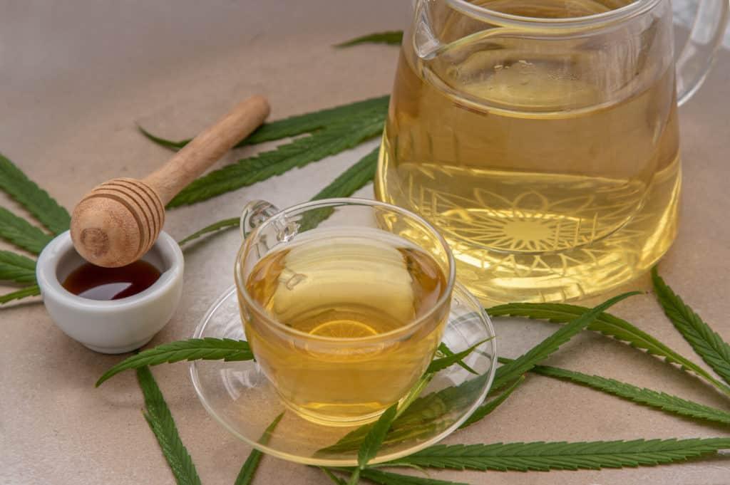 tea and marijuana leaves on table, marijuana stem tea