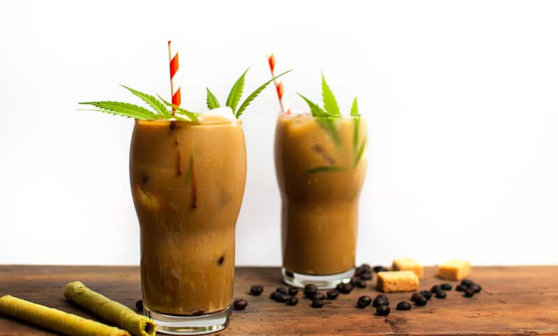 two glasses of coffee with marijuana leaves in them, marijuana butter coffee